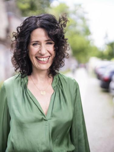 Portrait von Bettina Jarasch. Bettina blickt lachend in die Kamera. Im Hintergrund ist eine Straße zu sehen.