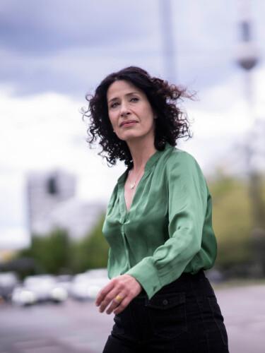 Bettina Jarasch geht auf einer Straße, im Hintergrund ist der Berliner Fernsehturm zu sehen