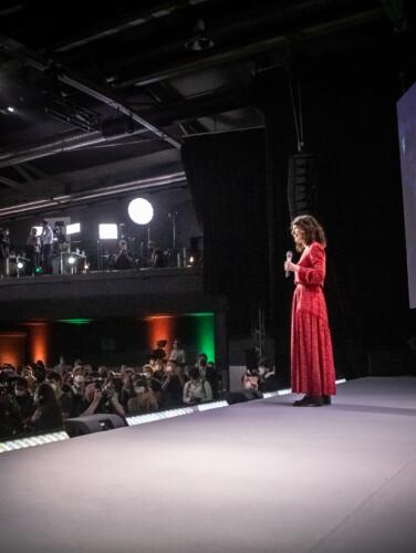 Bettina Jarasch steht auf einer Bühne in einem Konzertsaal, vor der Bühne stehen Menschen