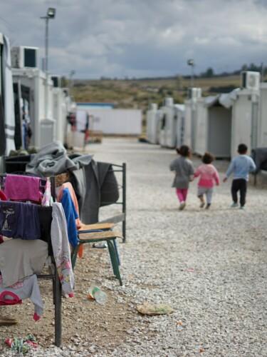 Kinder laufen auf einer Straße zwischen Wohncontainern