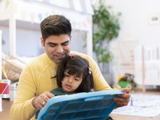 Lächelnder Mann lehrt Tochter auf Schiefer schreiben