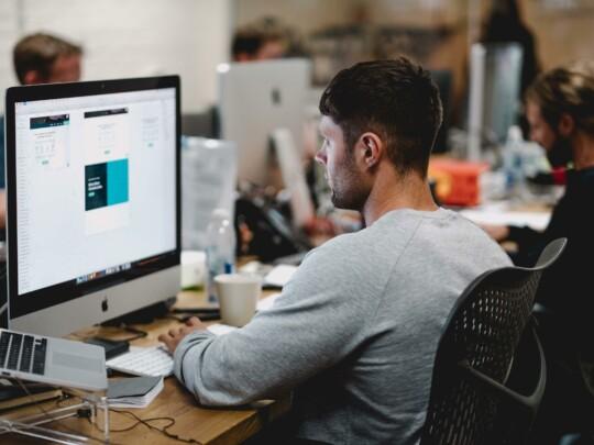Junger Mann vor iMac bei der Arbeit