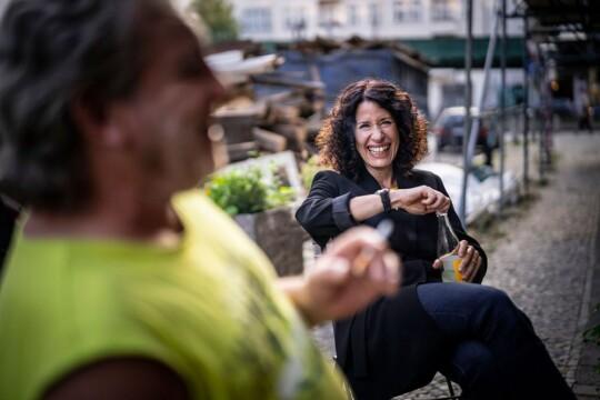 Bettina Jarasch sitzt, unterhält sich und lacht