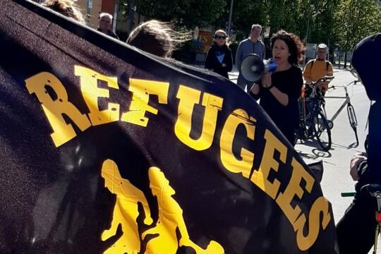 Bettina Jarasch spricht in ein Megafon auf einer Demonstration, Refugees Welcome Flagge