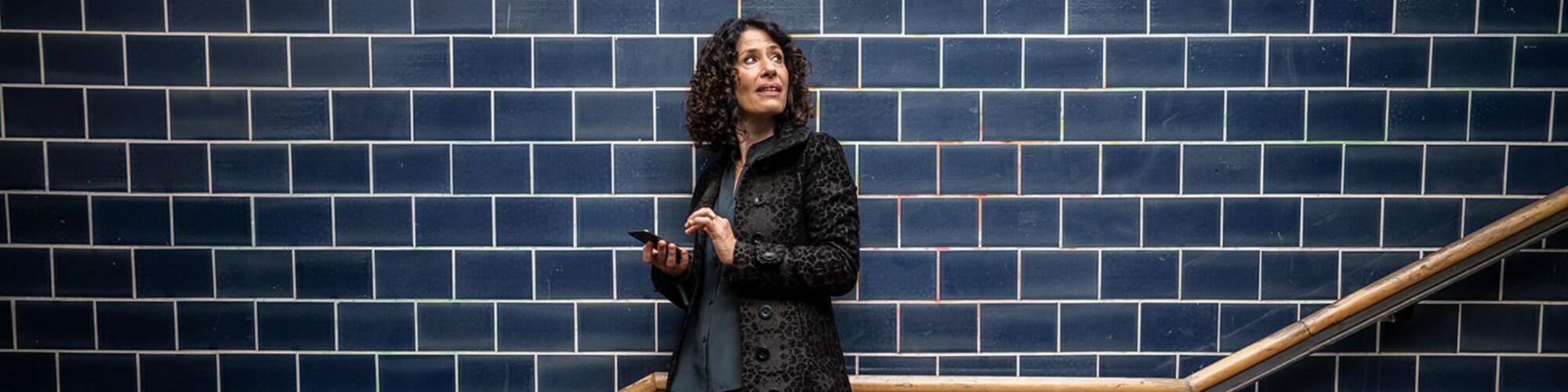 Bettina Jarasch steht am Treppengeländer im Bahnhof und schaut nach oben