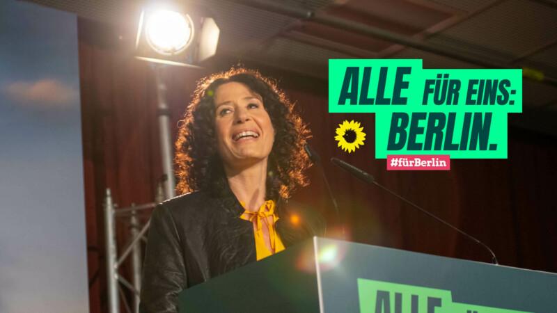 """Bettina Jarasch an einem Redepult, darauf die Aufschrift """"Alle für eins: Berlin. #fürBerlin"""""""