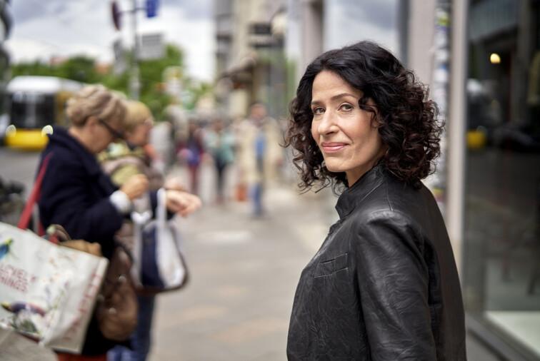 Bettina Jarasch geht auf einer belebten Straße und schaut über ihre Schulter in Richtung Kamera.