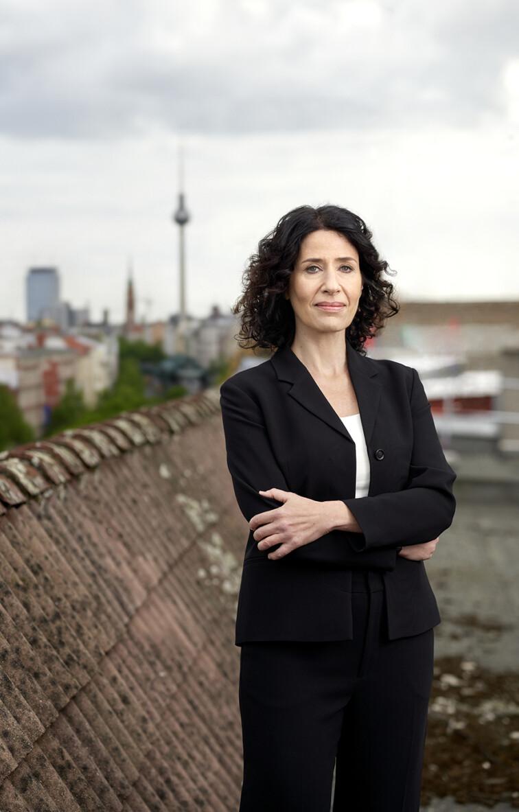 Bettina Jarasch steht mit verschränkten Armen auf einem Berliner Dach und blickt ernst in die Kamera