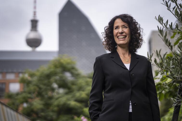 Bettina Jarasch steht auf einem begrünten Dach, im Hintergrund der Berliner Fernsehturm auf dem Alexanderplatz